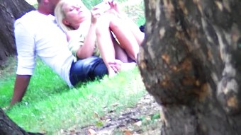 Blonde girl sitting upskirt in a park (no panties)